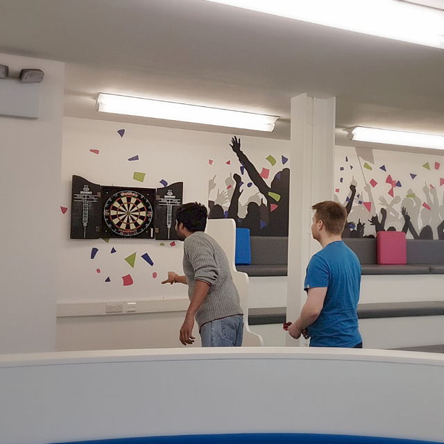 Playing darts in The Hub