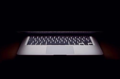 Laptop half closed in the dark