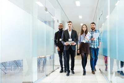 group of people walking in office together