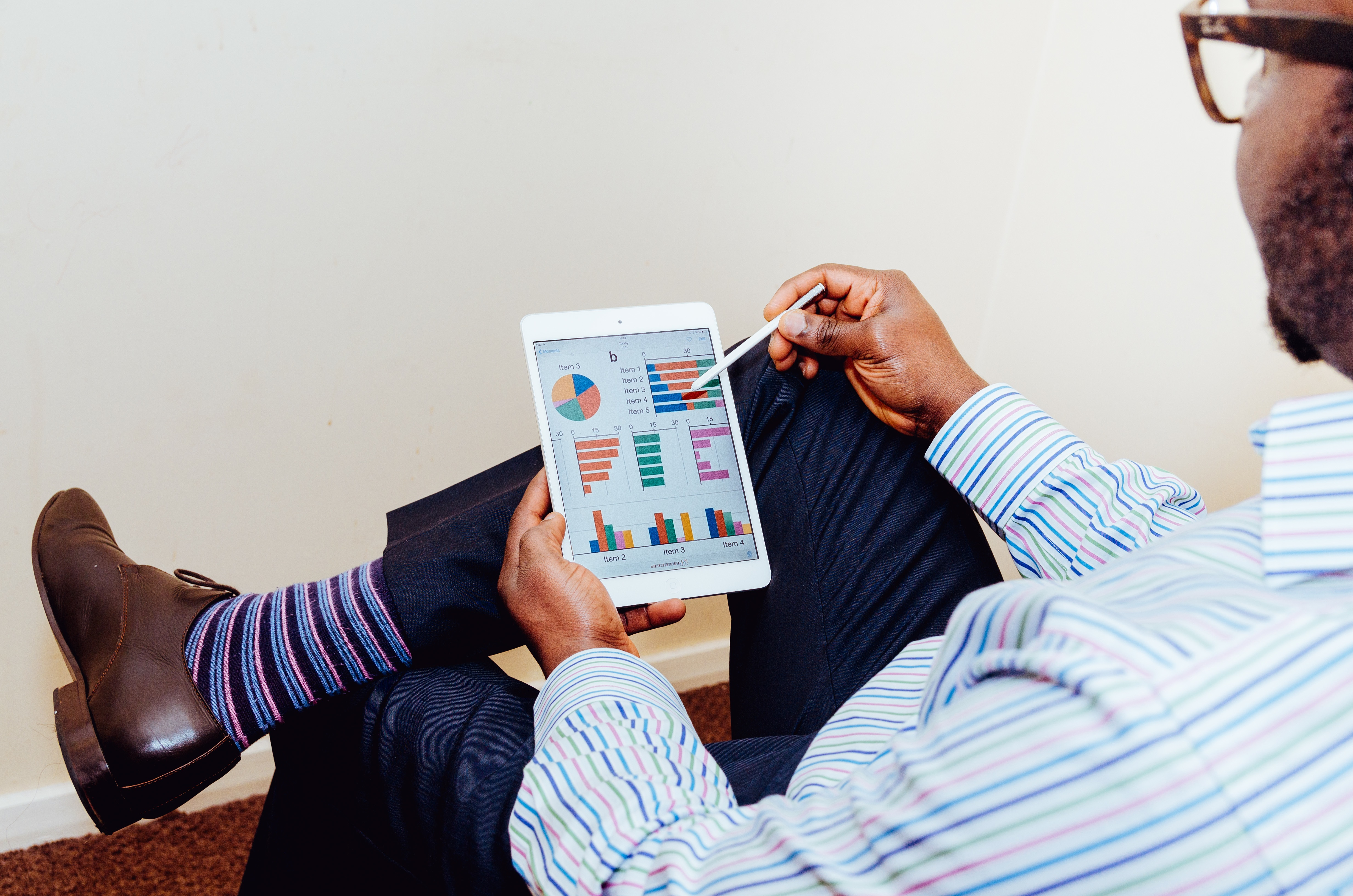 Man sat on chair looking at graphs on tablet