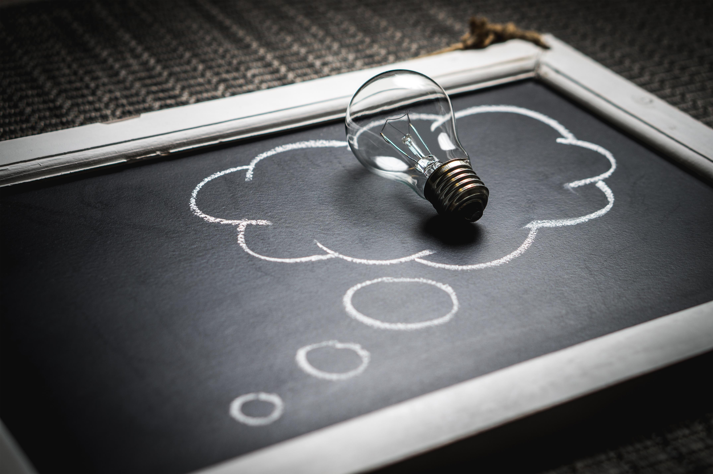 Light bulb inside thinking bubble on chalk board