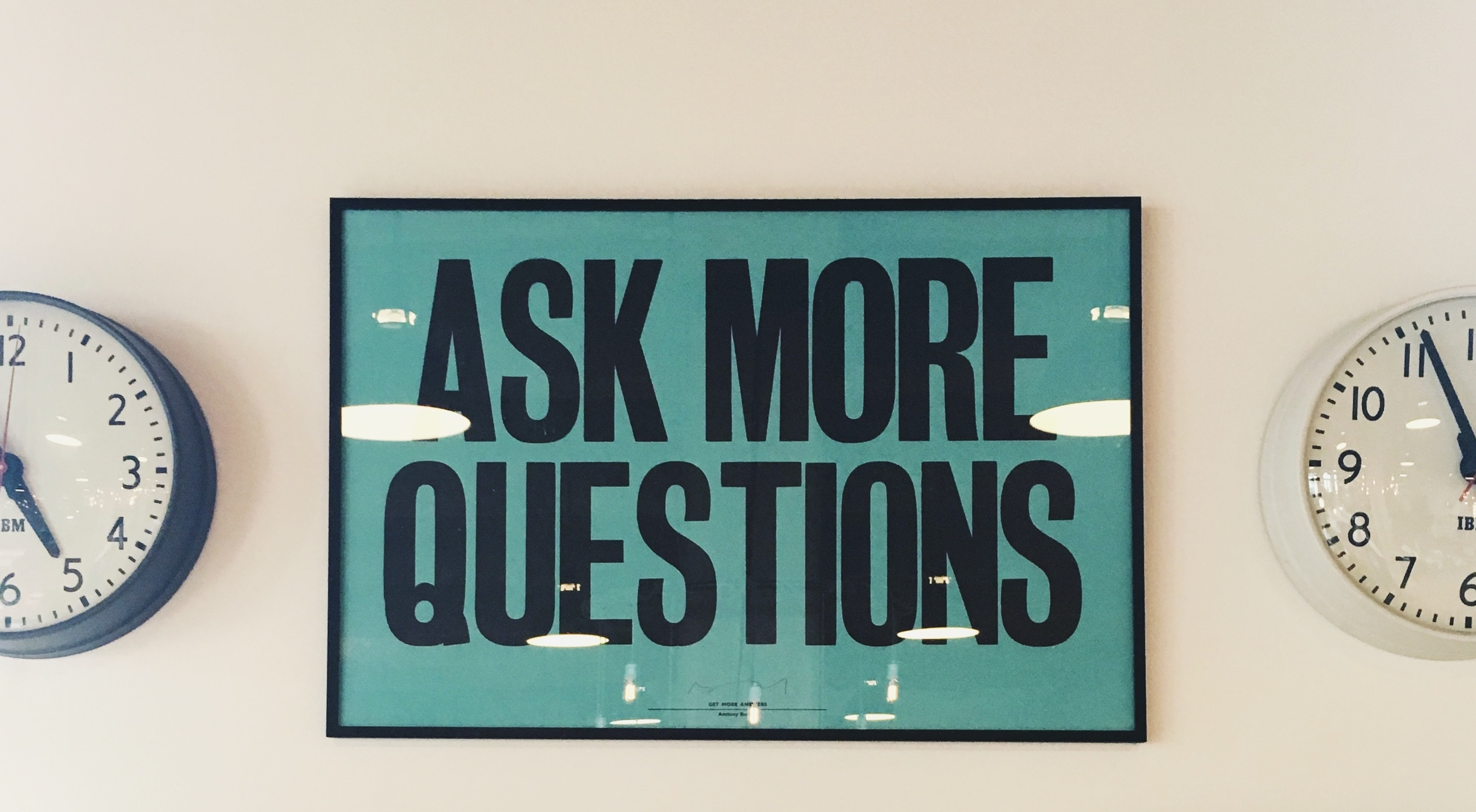 Ask more questions poster on wall