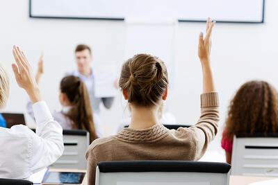 student raising hand to answer question in class