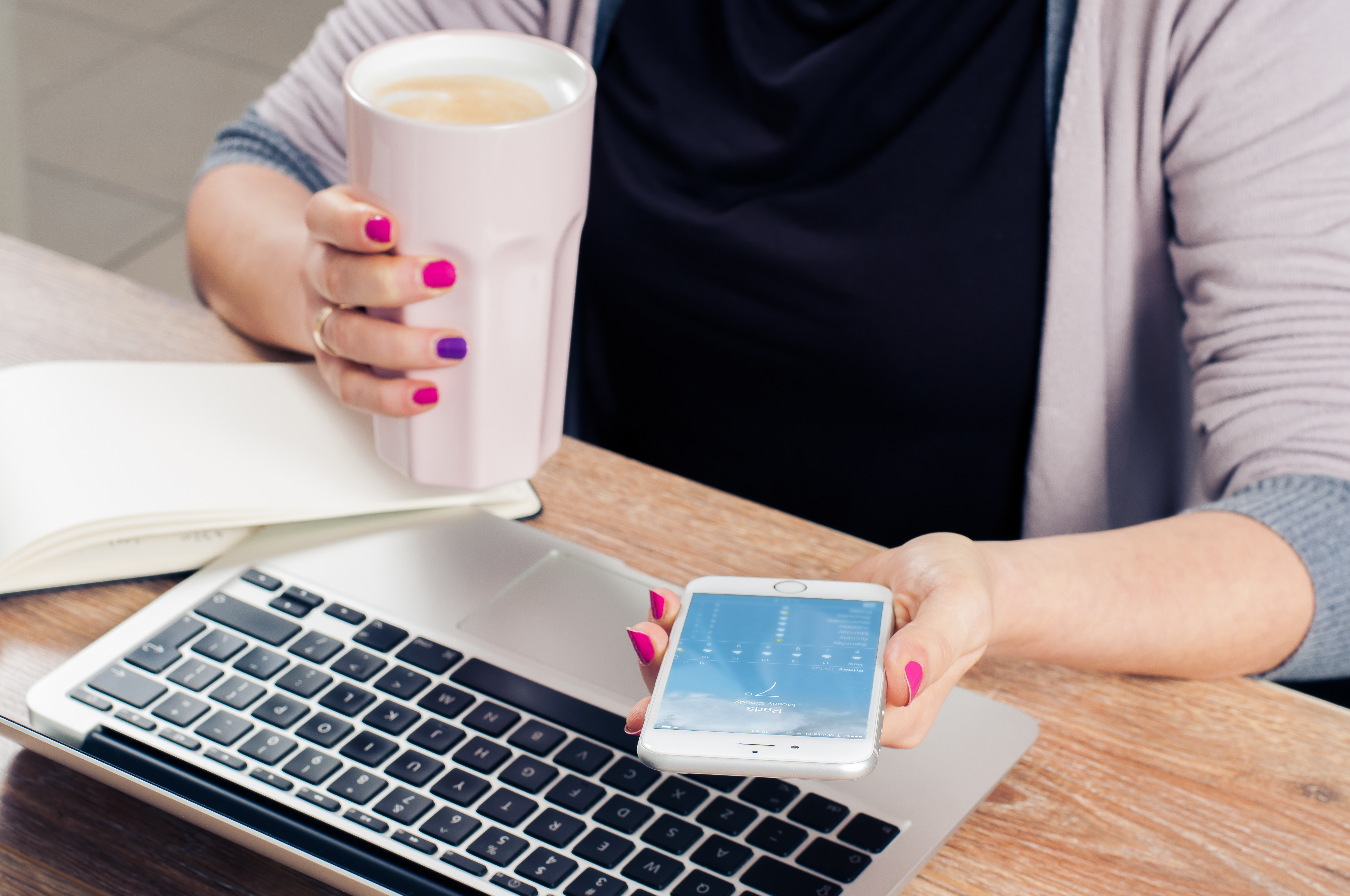 Woman with cup looking at mobile phone and working on laptop