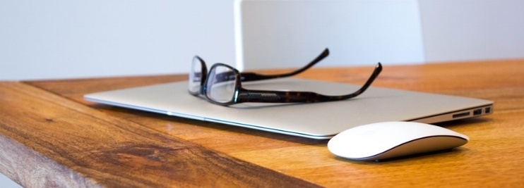 Laptop on desk with glasses on top