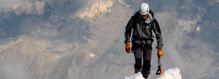 Man climbing up snowy mountain